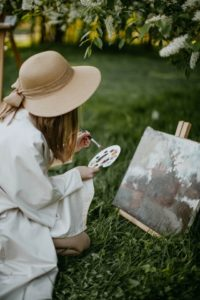lady painting in grass